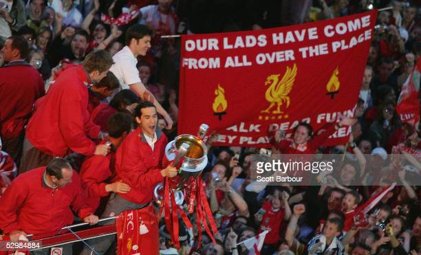 Luis Garcia lifts the trophy as the Liverpool team ride on an open top bus through a mass of fans on arrival at St George's Hall during the Liverpool...