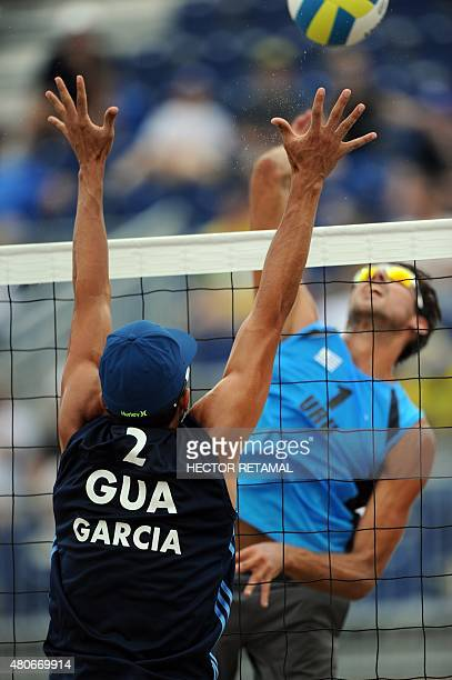 Luis Garcia of Guatemala tries to block the ball against Renzo Cairus of Uruguay during their men's Beach Volleyball Preliminary at the 2015 Pan...