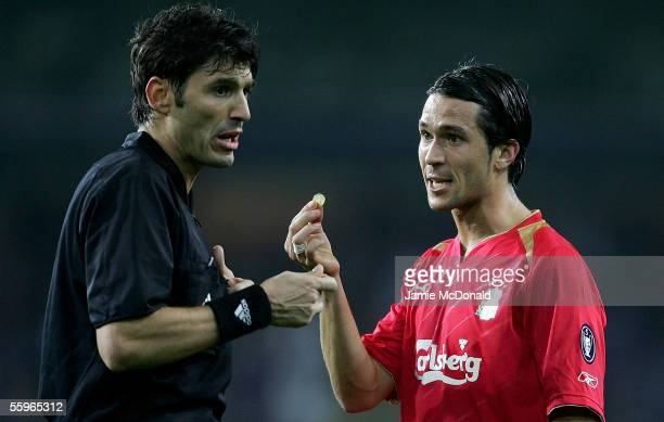 Luis Garcia of Liverpool shows the referee Massimo Busacca a coin that was thrown on to the pitch during the UEFA Champions League group G match...