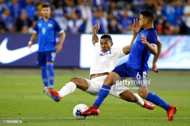 Luis Garrido of Honduras prepares to slide tackle as Narciso Orellana of El Salvador moves the ball down the field during the first half of Honduras...