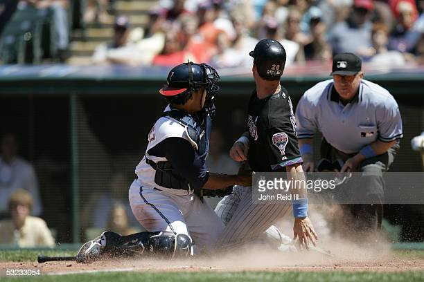 Luis Gonzalez of the Arizona Diamondbacks is involved in a close play at the plate with catcher Victor Martinez of the Cleveland Indians during the...