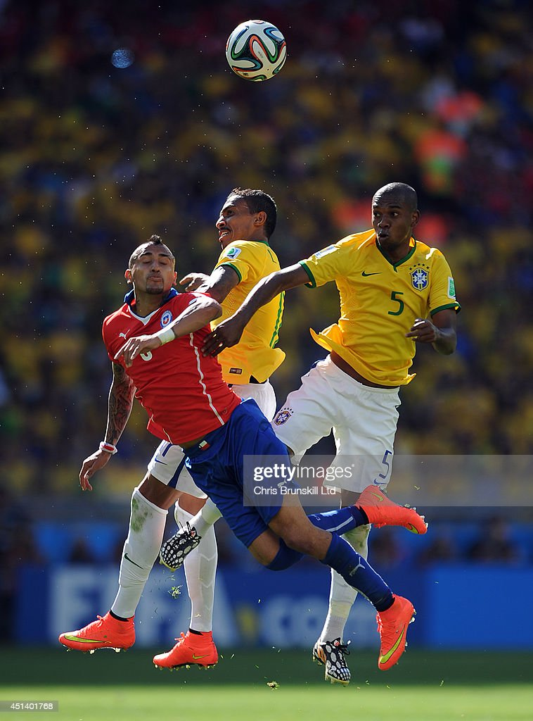 Luis Gustavo and Fernandinho of Brazil jump for a header with Arturo Vidal of Chile during the 2014 FIFA World Cup Brazil Round of 16 match between Brazil and Chile at Estadio Mineirao on June 28, 2014 in Belo Horizonte, Brazil.