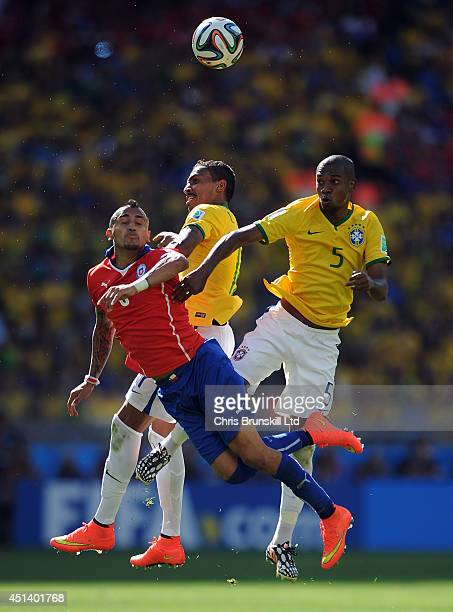 Luis Gustavo and Fernandinho of Brazil jump for a header with Arturo Vidal of Chile during the 2014 FIFA World Cup Brazil Round of 16 match between...