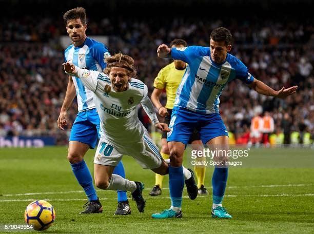 Luis Hernandez of Malaga CF makes penalty to Luka Modric of Real Madrid during the La Liga match between Real Madrid and Malaga at Estadio Santiago...