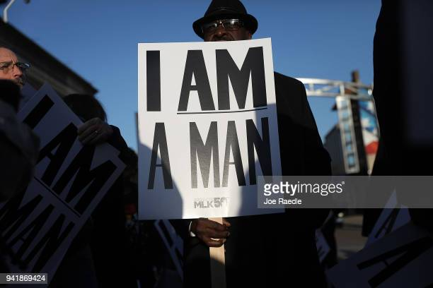 Luis Holmes holds 'I Am A Man' signs in reference to the sanitation workers strike in 1968 as he participates during an event to mark the 50th...
