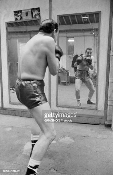 Luis MARIANO boxant avec Marcel CERDAN Jr encouragé par Annie CORDY encouragé par Annie CORDY Luis MARIANO de dos se reflétant dans le miroir auquel...