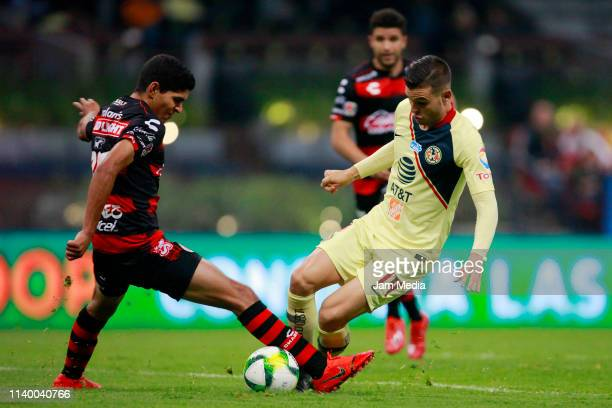 Luis Martinez of Tijuana fights for the ball with Nicolas Benedetti of America during the match between America and Tijuana as part of the Torneo...