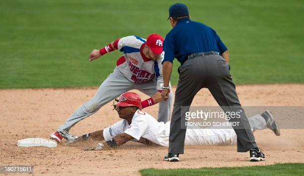 Luis Mateo of Criollos de Caguas of Puerto Rico tags out Jose Ramirez of Leones del Escogido of Dominican Republic during the 2013 Caribbean baseball...