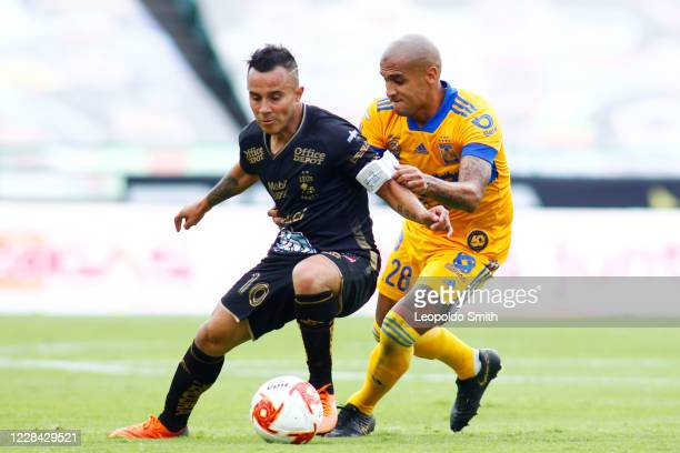 Luis Montes of Leon struggles for the ball with Luis Alfonso Rodriguez of Tigres UANL during the 9th round match between Leon and Tigres UANL as part...