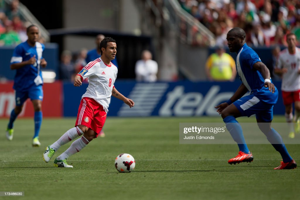 Luis Montes #8 of Mexico looks to make a pass against Jean-Sylvain Babin #22 of Martinique during the first half of a CONCACAF Gold Cup match at Sports Authority Field at Mile High on July 14, 2013 in Denver, Colorado.