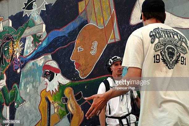 """Luis Moure, who was once addicted to K2 or """"spice"""", a synthetic marijuana drug, speaks with another man in East Harlem on August 5, 2015 in New York..."""
