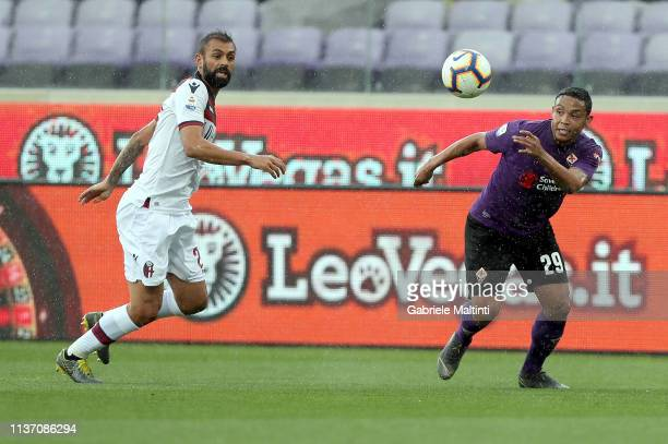 Luis Muriel of ACF Fiorentina battles for the ball with Danilo of Bologna FC during the Serie A match between ACF Fiorentina and Bologna FC at Stadio...