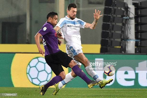 Luis Muriel of ACF Fiorentina compete for the ball with Francesco Acerbi of SS Lazio during the Serie A match between ACF Fiorentina and SS Lazio at...