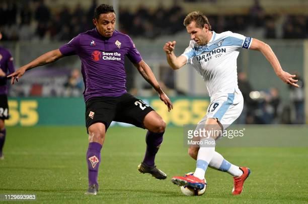 Luis Muriel of ACF Fiorentina compete for the ball with Senad Lulic of SS Lazio during the Serie A match between ACF Fiorentina and SS Lazio at...