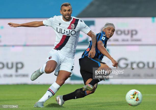Luis Muriel of Atalanta BC kicks the ball against Danilo Larangeira of Bologna FC and misses a chance of a goal during the Serie A match between...