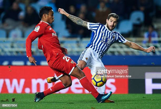 Luis Muriel of Sevilla FC competes for the ball with Inigo Martinez of Real Sociedad during the La Liga match between Real Sociedad and Sevilla at...