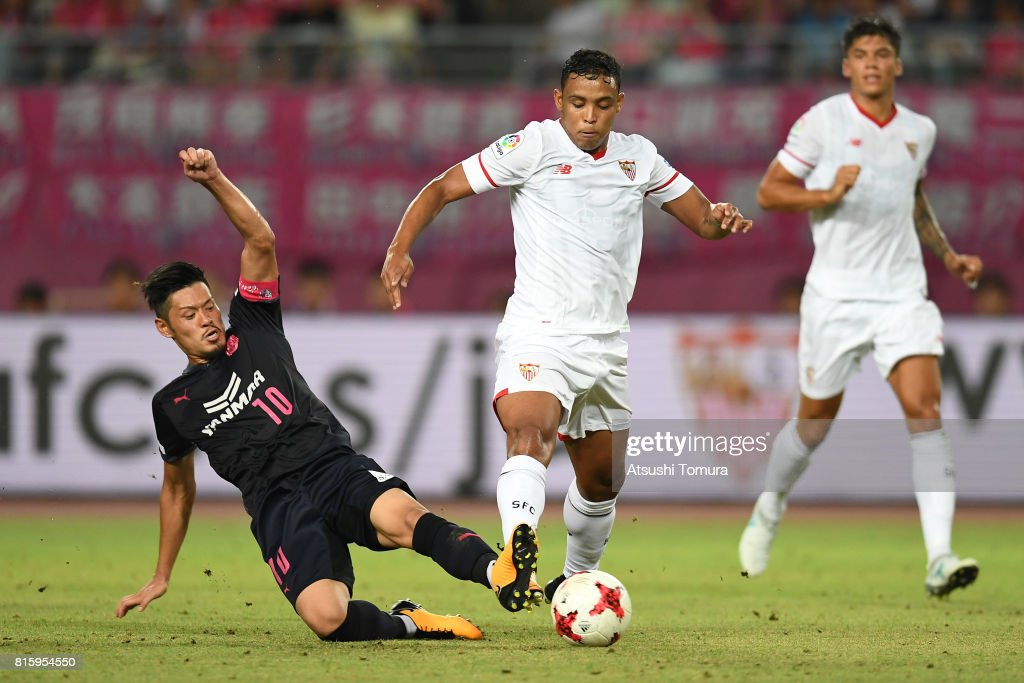 Luis Muriel of Sevilla FC (R) is tackled by Hotaru Yamaguchi of Cerezo Osaka (L) during the preseason friendly match between Cerezo Osaka and Sevilla FC at Yanmar Stadium Nagai on July 17, 2017 in Osaka, Japan.