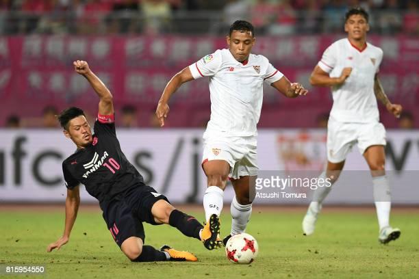Luis Muriel of Sevilla FC is tackled by Hotaru Yamaguchi of Cerezo Osaka during the preseason friendly match between Cerezo Osaka and Sevilla FC at...