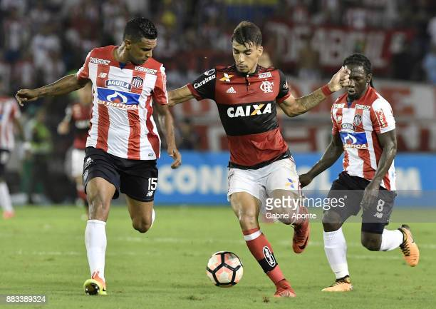 Luis Narvaez Pitalua and Yimmi Chara of Junior struggle for the ball with Lucas Paqueta of Flamengo during a second leg match between Junior and...