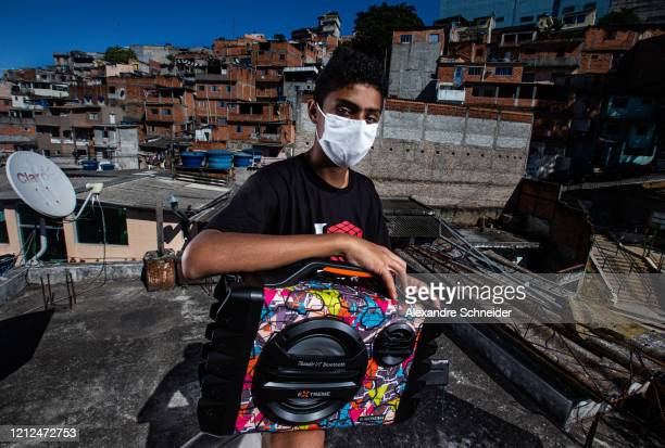 Luis Nascimento Ivan's son poses with the boombox used to conduct training sessions from the roof of his house to residents of Brasilandia amidst the...