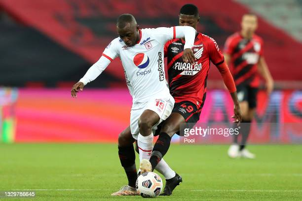 Luis Paz of America de Cali competes for the ball with Matheus Babi of Athletico Paranaense during a round of sixteen second leg match between...