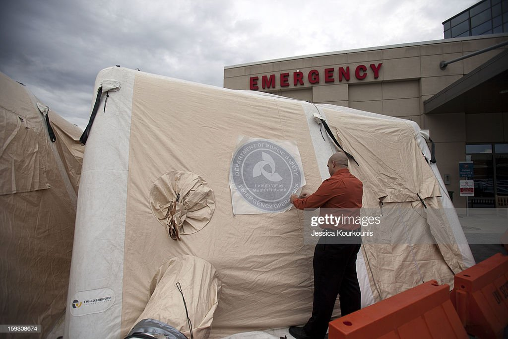 Luis Puentes, Director of Emergency Preparedness at Lehigh Valley Health Network's main hospital campus, applies a decal to a mobile tent set up to handle the recent influx of flu cases January 11, 2013 in Allentown, Pennsylvania. The health department has designated influenza as widespread throughout 41 states, with more than 11,000 laboratory-confirmed cases since flu season began in mid-December.