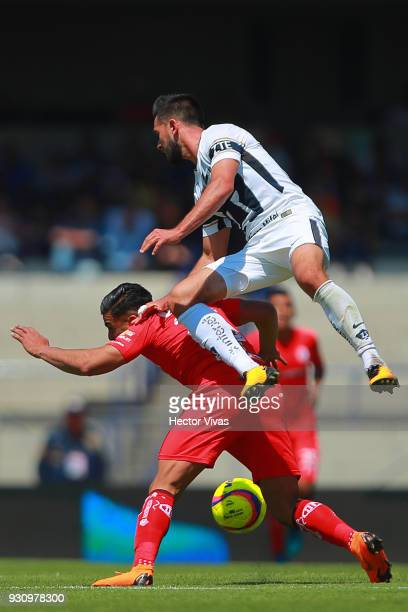Luis Quintana of Pumas struggles for the ball with Pedro Canelo of Toluca during the 11th round match between Pumas UNAM and Toluca as part of the...