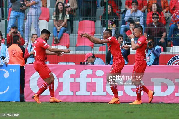 Luis Quiñones of Toluca celebrates with teammates Fernando Uribe and Pedro Canelo after scoring the second goal of his team during the 10th round...