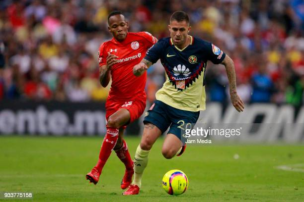 Luis Quiñones of Toluca fights for the ball with Jeremy Menez of America during the 12th round match between America and Toluca as part of the Torneo...