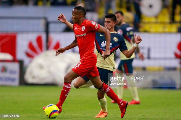 Luis Quiñones of Toluca fights for the ball with Joe Corona of America during the 12th round match between America and Toluca as part of the Torneo...