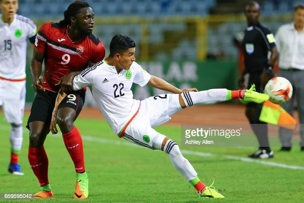 Luis Reyes kicks the ball as Kenwyne Jones of Trinidad battles for control during the fifth round match between Trinidad Tobago and Mexico as part of...