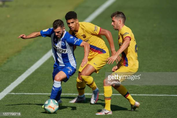 Luis Rioja of Alaves and Ronald Araujo and Sergi Roberto of Barcelona compete for the ball during the Liga match between Deportivo Alaves and FC...