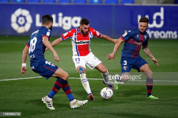 Luis Rioja of Deportivo Alaves and Pablo Maffeo and Dimitris Siovas of SD Huesca battle for the ball during the La Liga Santander match between SD...