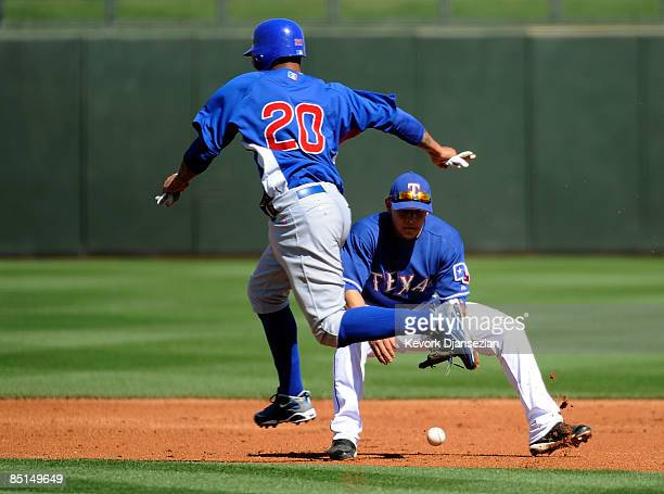 Luis Rivas of the Chicago Cubs jumps over the ball hit by teammate So Taguchi as German Duran of the Texas Rangers is unable to come up with the...