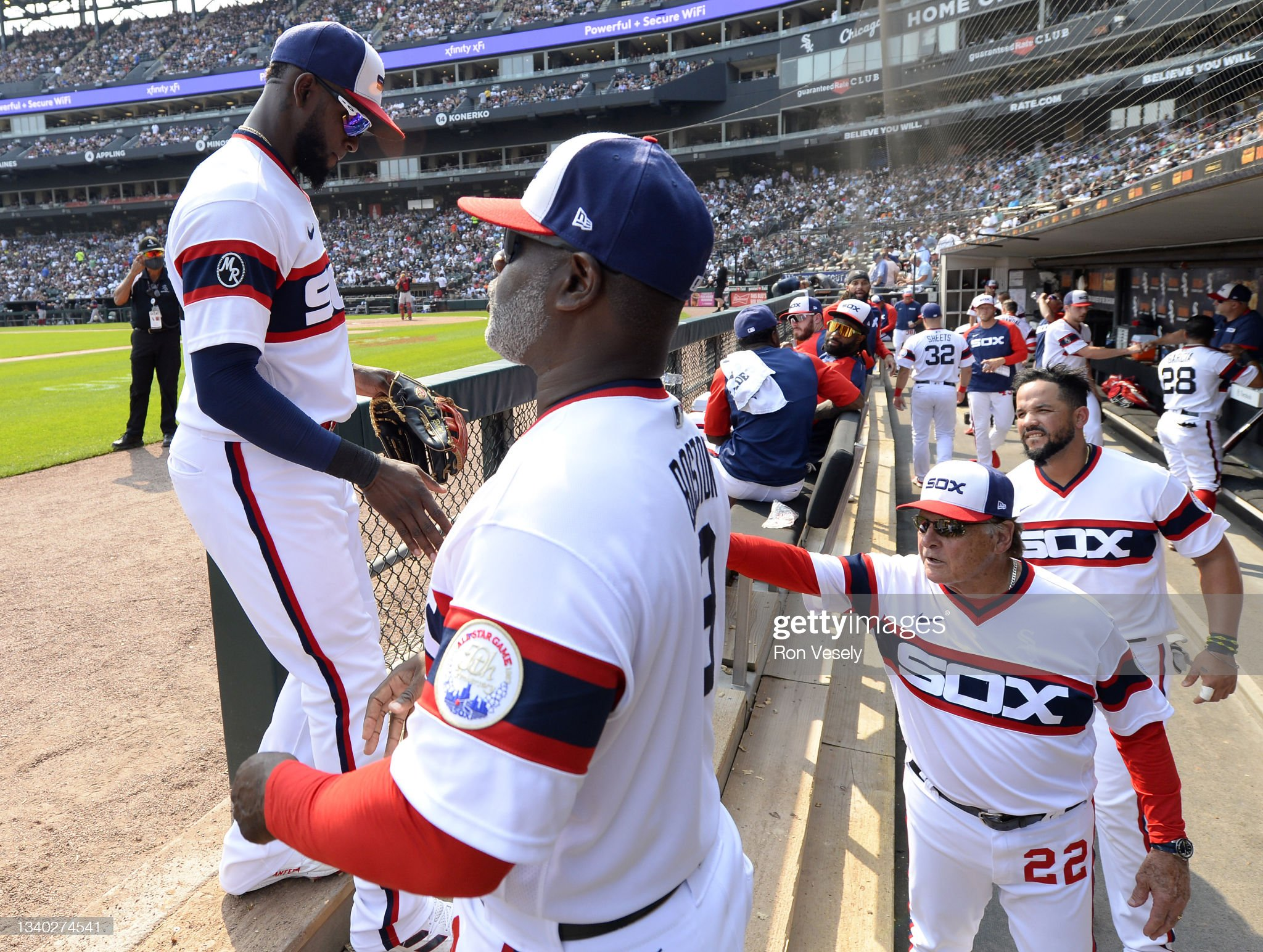 luis-robert-is-greeted-by-third-base-coa