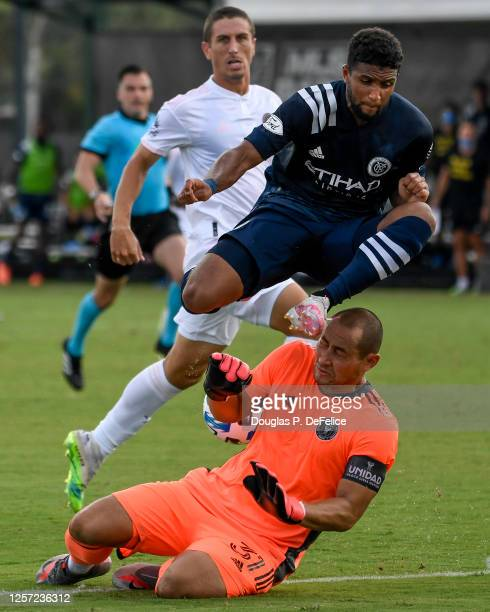 Luis Robles of Inter Miami CF makes a save as Ismael Tajouri of New York City FC leaps over to avoid contact during the second half in the MLS is...