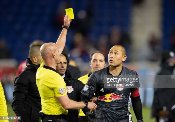 Luis Robles of New York Red Bulls gets a yellow card and his his shirt being pulled by Head Coach Chris Armas after the MLS match between Orlando...