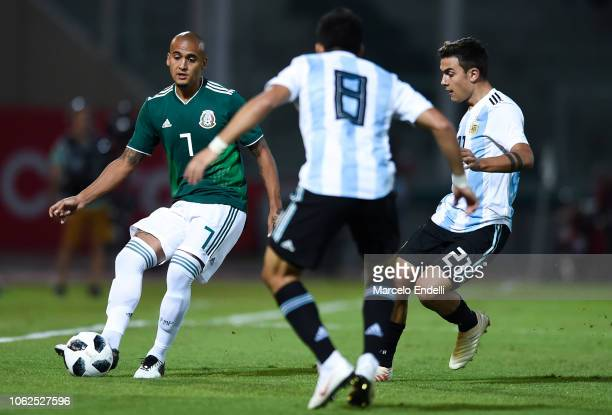 Luis Rodriguez of Mexico kicks the ball against Paulo Dybala of Argentina during a friendly match between Argentina and Mexico at Mario Kempes...