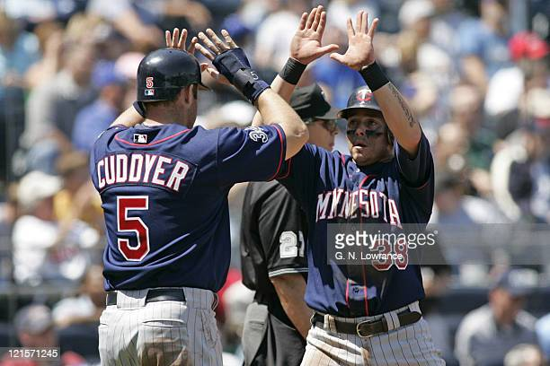 Luis Rodriguez of the Minnesota Twins is congratulated by Michael Cuddyer after scoring against the Kansas City Royals at Kauffman Stadium in Kansas...