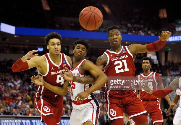Luis Rodriguez of the Mississippi Rebels competes for a rebound with Jamuni McNeace and Kristian Doolittle of the Oklahoma Sooners in the first half...