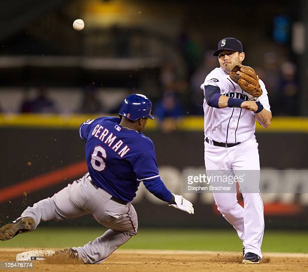 Luis Rodriguez of the Seattle Mariners turns a double play after forcing out Esteban German of the Texas Rangers during a game at Safeco Field on...