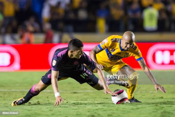 Luis Rodriguez of Tigres fights for the ball with Angel Zaldivar of Chivas during the 12th round match between Tigres UANL and Chivas as part of the...