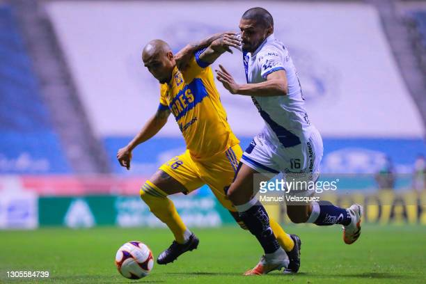 Luis Rodriguez of Tigres struggles for the ball against Juan Segovia of Puebla during the 10th round match between Puebla and Tigres UANL as part of...