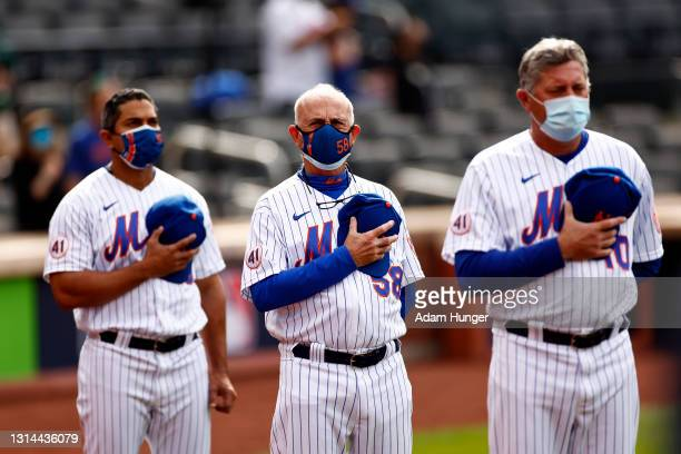 Luis Rojas of the New York Mets, Dave Jauss of the New York Mets and Gary Disarcina of the New York Mets stand for the national anthem before taking...