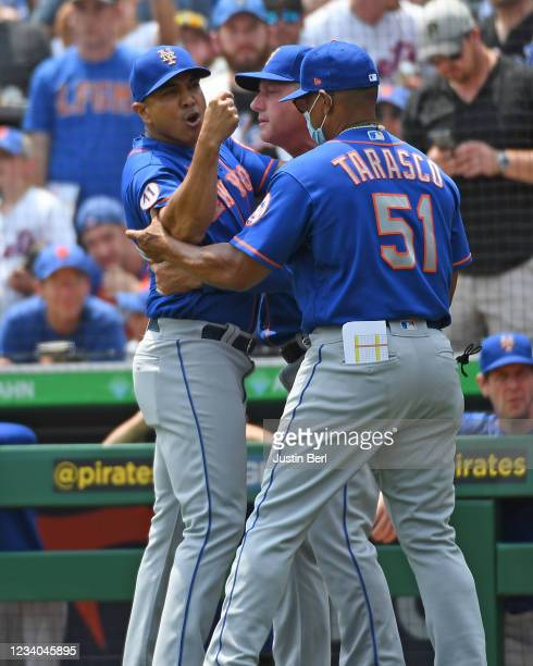 Luis Rojas of the New York Mets is restrained by Tony Tarasco as he argues with home plate umpire Jeremy Riggs after a close play at home plate in...