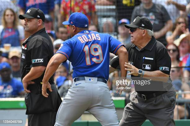 Luis Rojas of the New York Mets is restrained by umpire Larry Vanover as he argues with home plate umpire Jeremy Riggs after a close play at home...