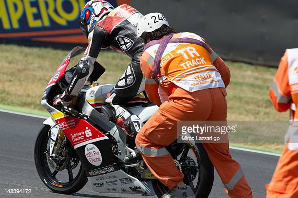 Luis Rossi of France and Racing Team Germany is assisted by a marshall during the Moto3 race of the MotoGP of Italy at Mugello Circuit on July 15...