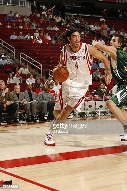 Luis Scola of the Houston Rockets drives past Dimitrios Diamantidis of Euroleague champion Panathinaikos October 11, 2007 at the Toyota Center in...
