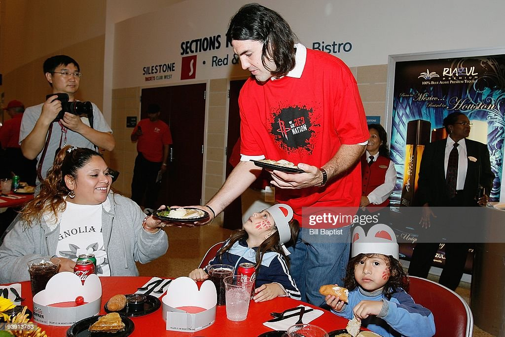 Luis Scola of the Houston Rockets serves meals to children from the