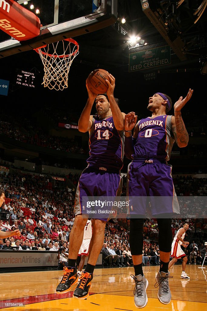 Luis Scola #14 of the Phoenix Suns grabs a rebound over his team mate Michael Beasley #0 of the Phoenix Suns during a game on November 5, 2012 at American Airlines Arena in Miami, Florida.